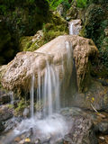 Small waterfall on brown stone. Small waterfall running from rock in shadow forest Stock Images