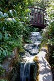A wooden bridge over a waterfall stock photo