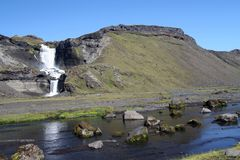 Small waterfall cascade on Iceland into river with boulders royalty free stock image