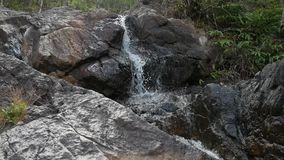 Small waterfall cascading over rocks in tropical forest. hd slow motion. thailand. stock footage