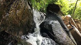 Small Waterfall Cascading over Rocks in Tropical Forest. HD slow motion. Thailand. stock video