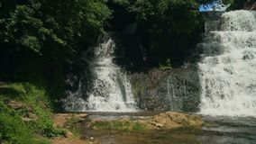 Small Waterfall Cascading over Rocks in Tropical Forest. Slow motion stock video