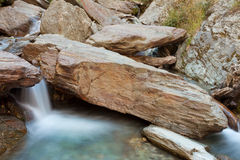 Small waterfall casdcading over rocks in blue pond Stock Images