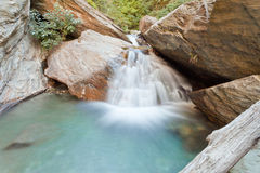 Small waterfall casdcading over rocks in blue pond Royalty Free Stock Photos
