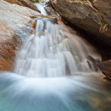Small waterfall casdcading over rocks in blue pond Stock Photo