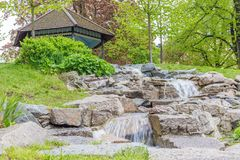 Small Waterfall Close to a Gazebo. A Small Waterfall Close to a Wooden Gazeebo on a Hille Stock Image