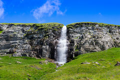 Small waterfall coming down from a plateau with a blue sky above Royalty Free Stock Photography