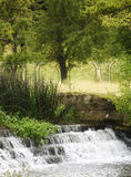 Small Waterfall in the English Countryside. Stream waterfall, English countryside with trees Royalty Free Stock Photo