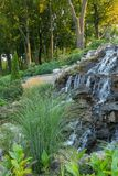 A small waterfall that flows down a stony slope in the middle of a green park in sunny weather. resting-place. For your design royalty free stock images