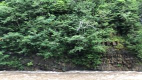 A small waterfall flows into the swift mountain river. stock video footage