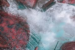 Small waterfall in the foreground with rocks of red tones and crystal clear water of blue colors stock photography