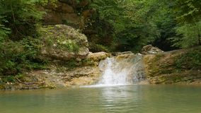 Small waterfall in forest stock video footage