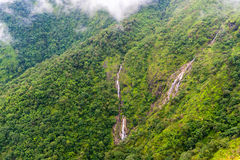 Small waterfall on green mountain ridge in rain forest Royalty Free Stock Image