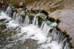 A Small Waterfall In a Local Stream. Clear flowing water over a waterfall in a local park creek with brown rock bottom and bubbles floating on water Royalty Free Stock Photos