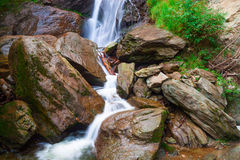 Small waterfall on a mountain rive. R between rocks royalty free stock image