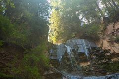 Small waterfall on small mountain stream. Water streams with sun rays,. Small waterfall on small mountain stream in Kyrgyzstan. Water streams with sun rays Royalty Free Stock Photos