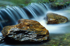 Small waterfall and a pair of river rocks royalty free stock photo