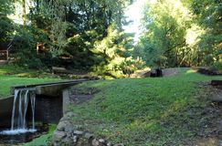 Small waterfall in a public park. Small waterfall flowing in a public park against a green lawn background royalty free stock images