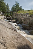 Small waterfall, rapid stream running over rocks. Summer day, su Stock Photography