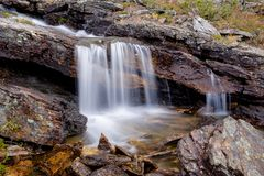Small waterfall. A small waterfall in a river flowing at the bottom of a canyon in the Urho Kekkonen National Park of the Finnish Lapland Royalty Free Stock Photos