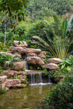 Small Waterfall from Rock Mountain in a Green Tropical Background Stock Photography