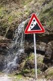 Small waterfall running behind a landslide sign. Outdoors Royalty Free Stock Images