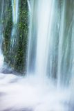 Small waterfall on small mountain stream, mossy sandstone block. Clear cold water is hurry jumping down into small pool. Royalty Free Stock Photo