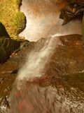 Small waterfall on small mountain stream, mossy sandstone block and water is jumping down into small pool. Water streams with sun. Royalty Free Stock Photos