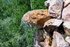 A small waterfall sprinkles drops of water down royalty free stock photo