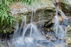 Small waterfall in steam in public park Royalty Free Stock Images