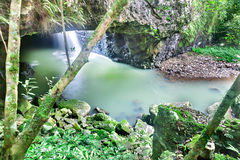 Small waterfall in a stone cave with moss rocks Royalty Free Stock Images