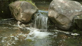 Small waterfall between the stones stock footage