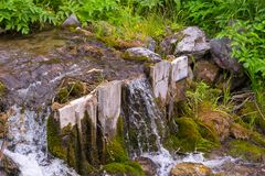 A small waterfall between the stones and two wooden planks among stock photo