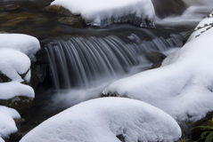 Small waterfall on a stream covered in snow Royalty Free Stock Photos