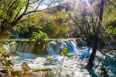Small waterfall with sunlight rays Royalty Free Stock Images