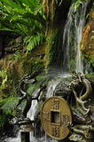 Small waterfall and traditional chinese temple statues. Royalty Free Stock Photography