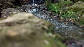 Small waterfall. Water flow from a small artificial waterfall inside park stock video
