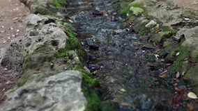 Small waterfall. Water flow from a small artificial waterfall inside park stock video footage