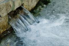 A small waterfall of water over the eye of a clear river water stock image