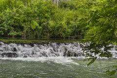 Small waterfall on a wide river, dam. France Royalty Free Stock Photo