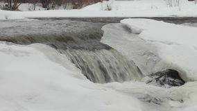 A small waterfall on a winter day stock footage