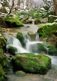 Small waterfall on winter stream Royalty Free Stock Images
