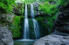 Small waterfall in wood. A long-exposure shot of a small but relatively long waterfall among some rocks and moss stock image