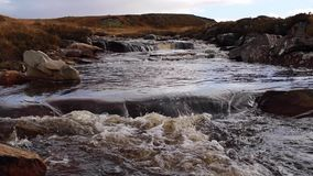 Small waterfalls and flow along a high scottish highlands river in sutherland during november. stock video footage
