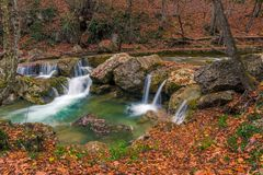 Small waterfalls and a river postcard view in a beautiful natural location in the autumn mountain. Forest royalty free stock photography
