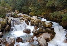 Small waterfalls and River rapids. A river forms small cascades and rapids as it flows over a stoney valley floor in the Everest region of the Himalayas, Nepal Royalty Free Stock Photo
