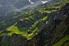 Small waterfalls on summer green hills in Alps Valley Stock Photo