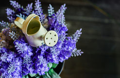 A small watering can on the artificial lavender Stock Photo