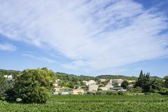 Small wave of beautiful white fluffy clouds on vivid blue sky in a summer time above houses on the mountain, vineyard. And green trees in Vacqueyras village of stock image