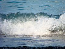 The wave breaks at the shore. A small wave breaks near a rocky shore on a quiet day stock photos